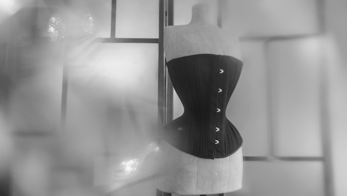 This bespoke piece in black spot broche is for a lady with quite a long torso, hence it looking like a midbust on the mannequin. That is indeed one of the challenges of international/distance bespoke orders, you are always wishing you could be there for in-person fittings.