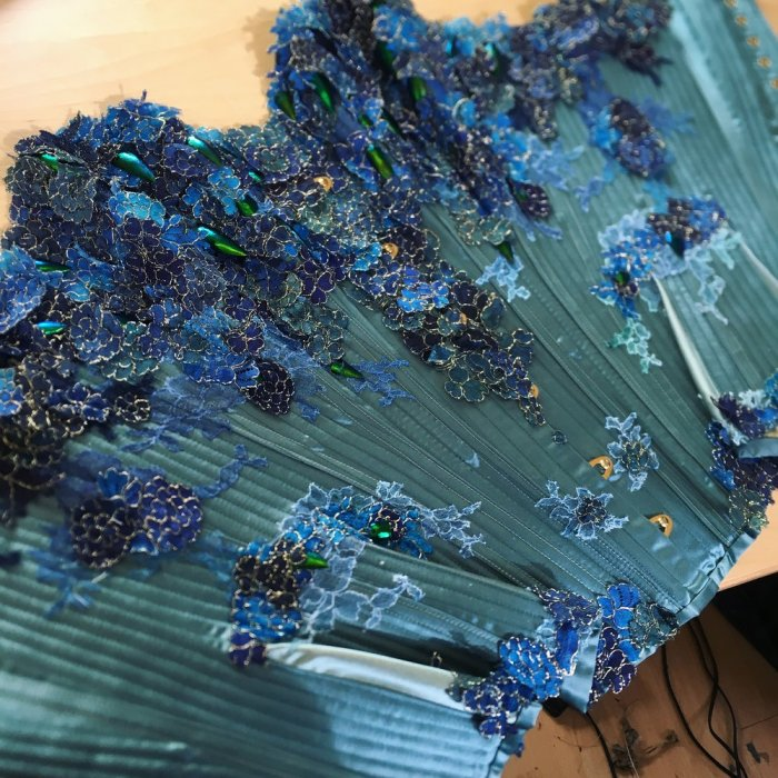 This delicious corset is made from our favourite silk duchess in two tones, with hand-painted lace layered up for luscious effect. Electra beetle wings are scattered amongst the lace, some cut and some in their natural shape. Our client gave us lots of colour inspiration for this piece, many lagoon blues and greens... But behind that we also have a deeper inspiration, that of rebirth, self-creation, and daily new beginnings. Hence the scarab reference point which led us to focus on a symmetrical design.